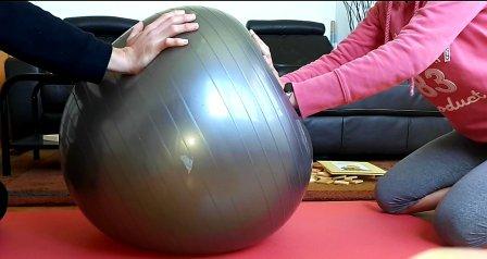 Imagen de persona empujando pelota grande